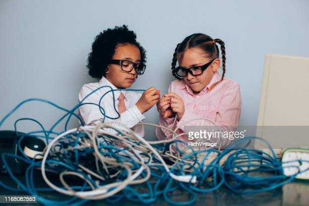 young girl it professionals are fixing computer problems - adult imitation stock pictures, royalty-free photos & images