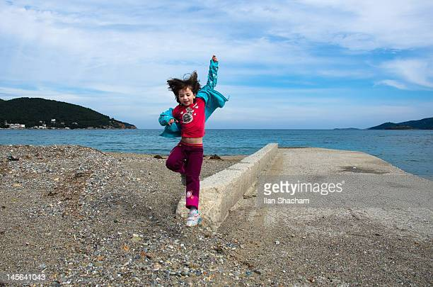 Young girl jumping and having fun on beach