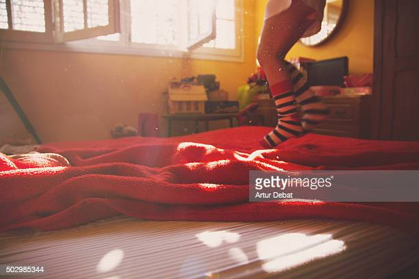 Young girl jumping and playing on the bed with colorful socks and nice light.