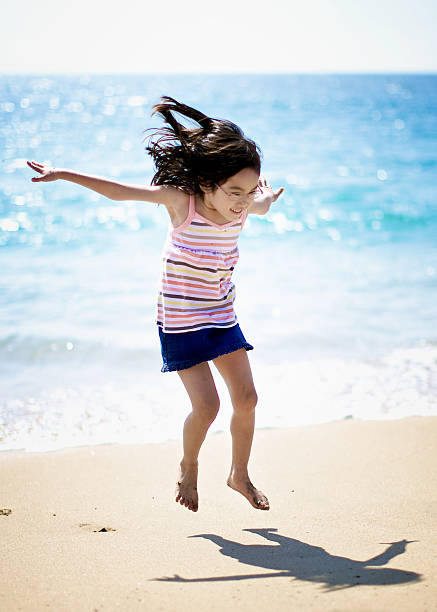 Young girl jumping at the beach near the sea