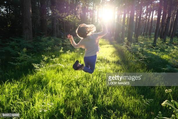 a young girl jumping for joy in a sunlit forest - ein mädchen allein stock-fotos und bilder