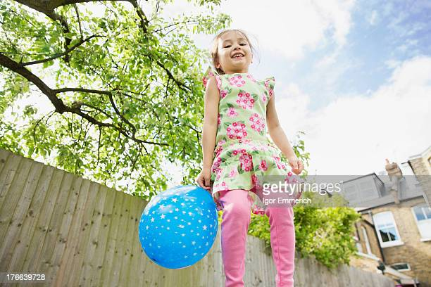 Young girl jumping in garden with balloon