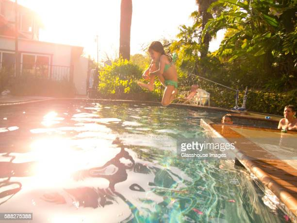 young girl jumping in pool with sun flare - canon stock pictures, royalty-free photos & images