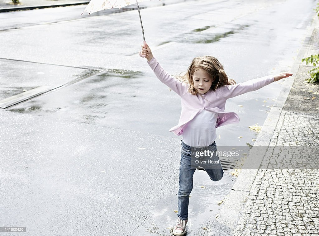 A young girl jumping in puddles : Stock Photo