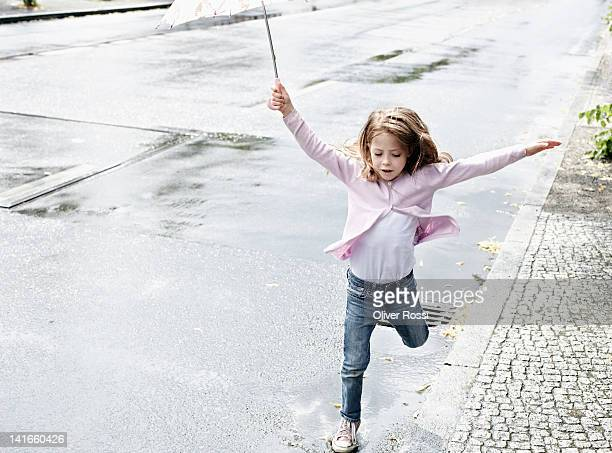 A young girl jumping in puddles