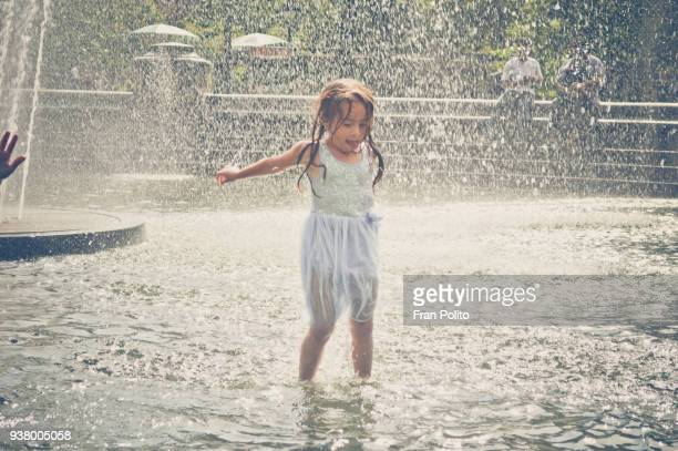 a young girl jumping in the water in a park fountain. - hot young girls stock photos and pictures