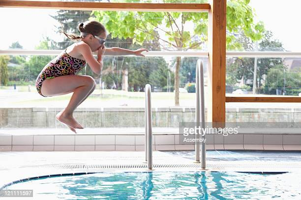 young girl jumping into pool - 鼻をつまむ ストックフォトと画像