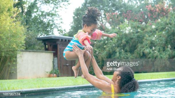 Young Girl Jumping into Swimming Pool