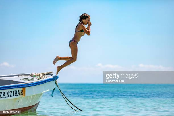young girl jumping off a small boat on zanzibar - zanzibar island stock photos and pictures