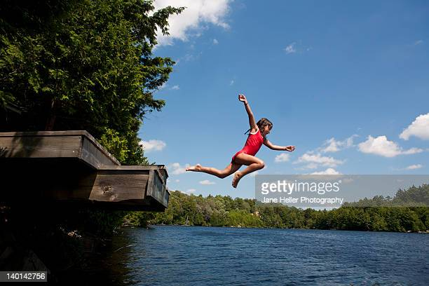 Young girl jumping off high dock