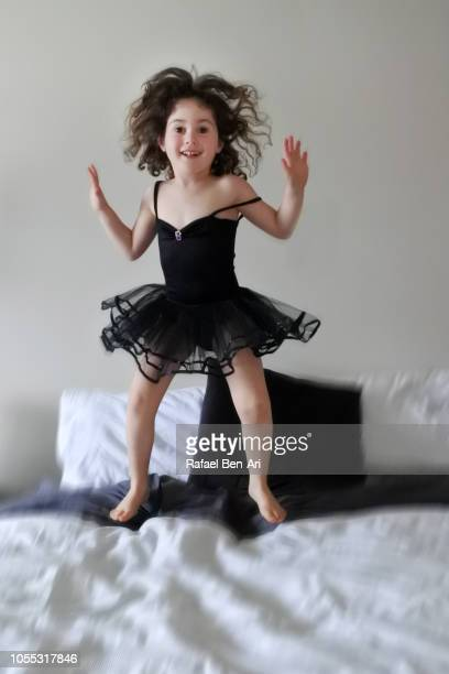 Young Girl Jumping on a Bed