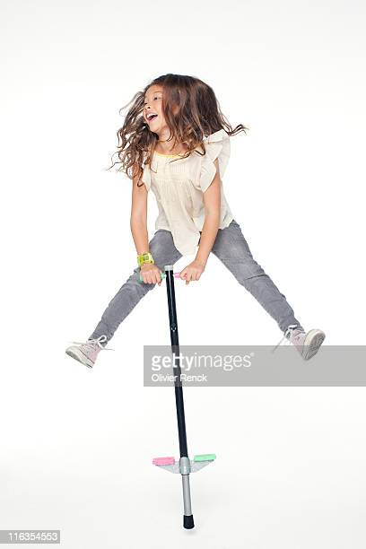A young girl jumping on a pogo stick.