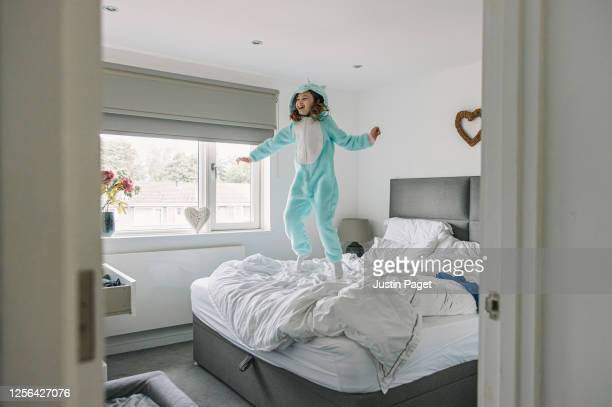 young girl jumping on parents' bed - freedom stock pictures, royalty-free photos & images