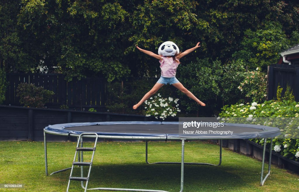 Young girl jumping on trampoline with Panda mask on. : Stock Photo