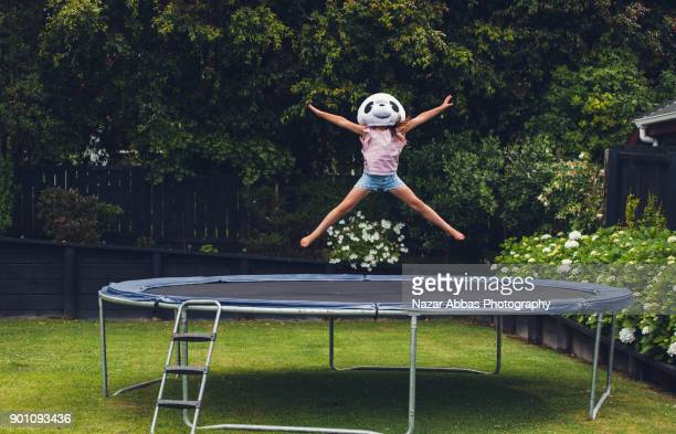 young girl jumping on trampoline with panda mask on. - panda animal stock photos and pictures