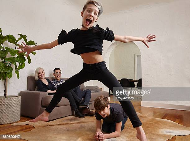 Young girl jumping over brother.