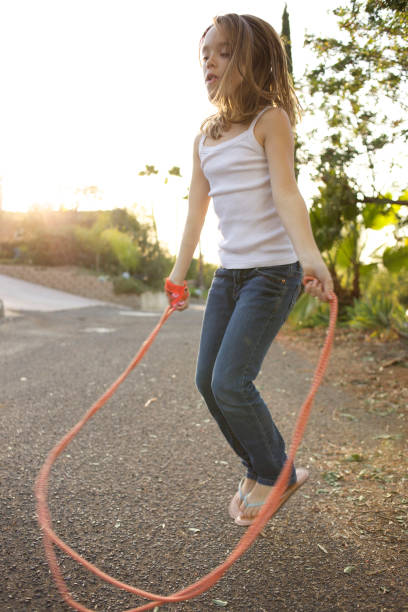 Young girl jumping rope on the street.