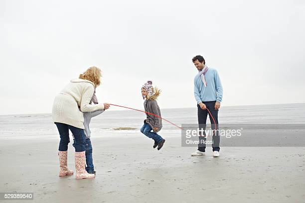 Young girl jumping rope with her family on a beach