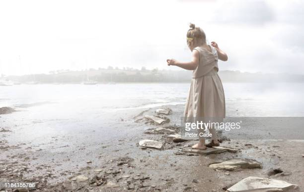 young girl jumping stepping stones along river bed - head of state stock pictures, royalty-free photos & images