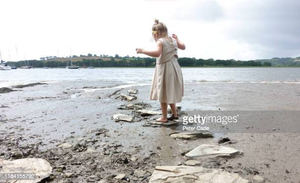 young girl jumping stepping stones along river bed - direction stock pictures, royalty-free photos & images