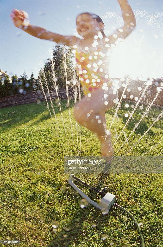 Young Girl Jumping Through a Garden Sprinkler : Stock Photo