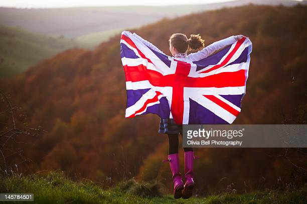 young girl jumping with union jack - union jack stock photos and pictures