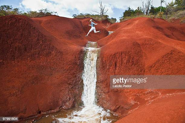 young girl jumps across a creek - waimea canyon stock pictures, royalty-free photos & images