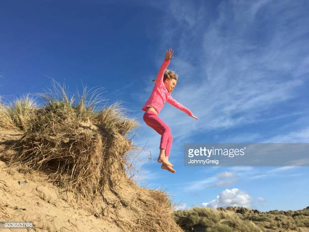 Young girl jumps from sand dune