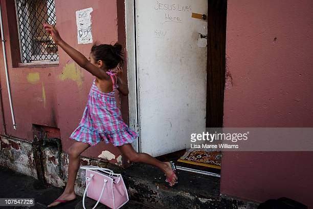 """Young girl jumps from the doorway of a home on Vine Street in the Aboriginal housing community known as """"The Block"""" in Sydney, Australia...."""