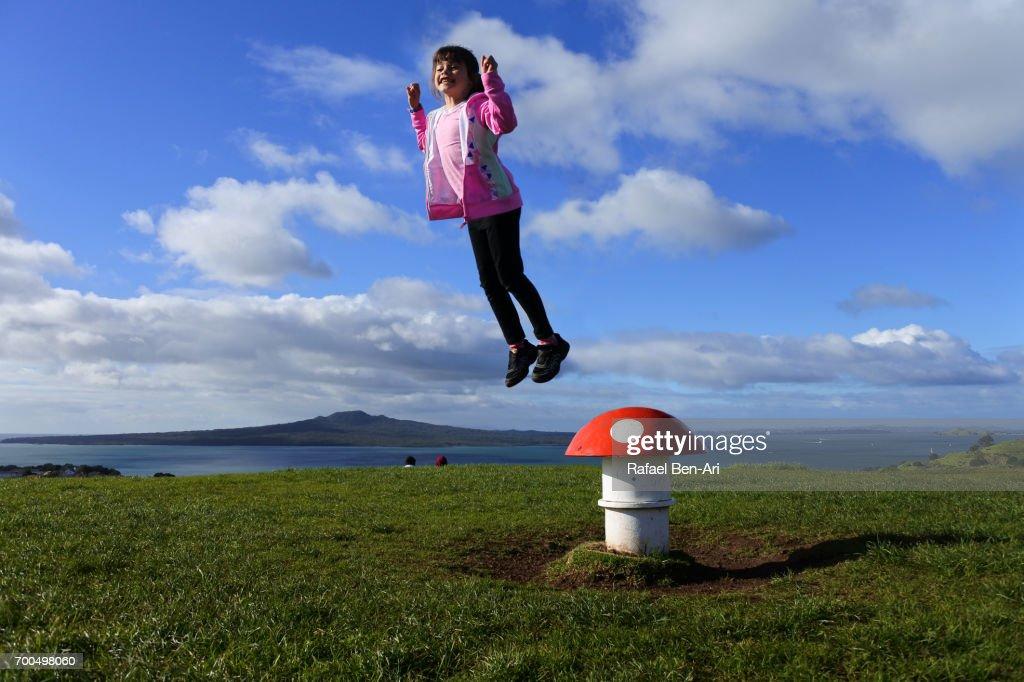 Young girl jumps over magic mushroom : Stock Photo