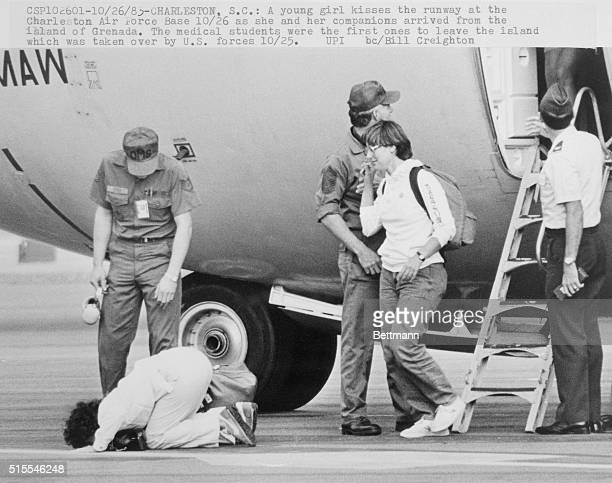 A young girl kisses the runway at the Charleston Air Force Base here as she and her companions arrived from the island of Grenada The medical...