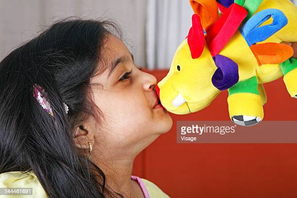 Young girl kissing a soft toy