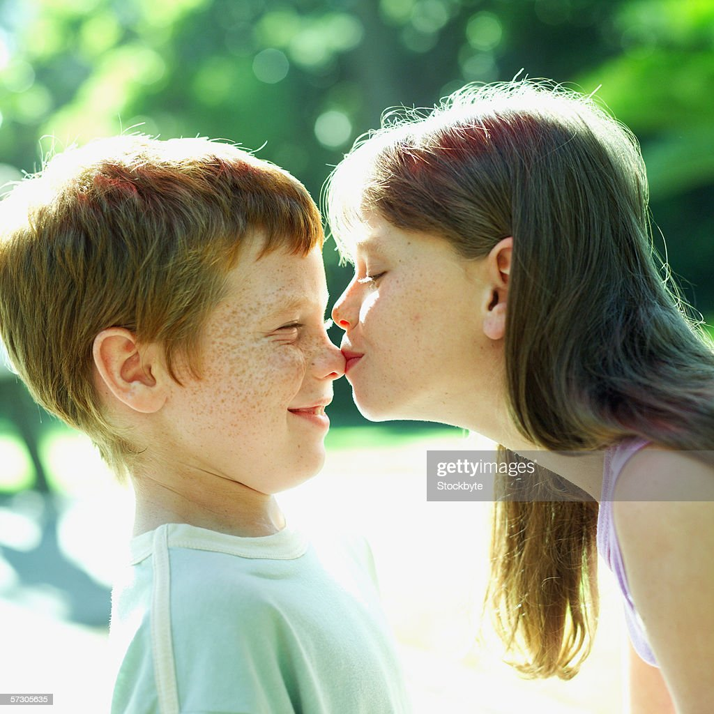 Young Girl Kissing A Young Boy On His Nose Stock Photo -4335