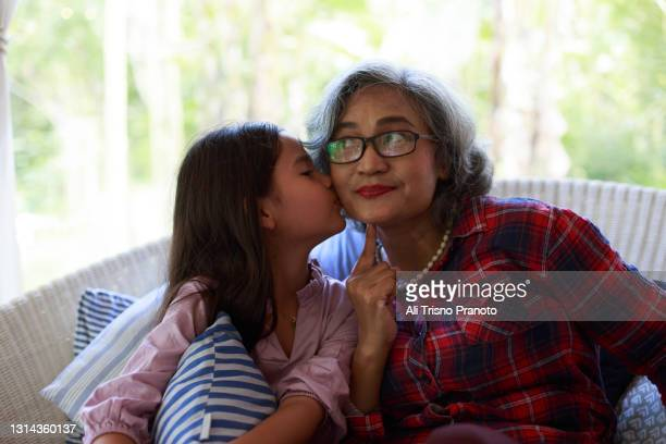 young girl kissing her grandmother, asian family, in sofa - moment of silence stock pictures, royalty-free photos & images