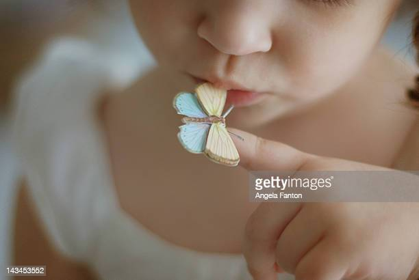 young girl kissing paper butterfly - arabian girl kissing stock photos and pictures