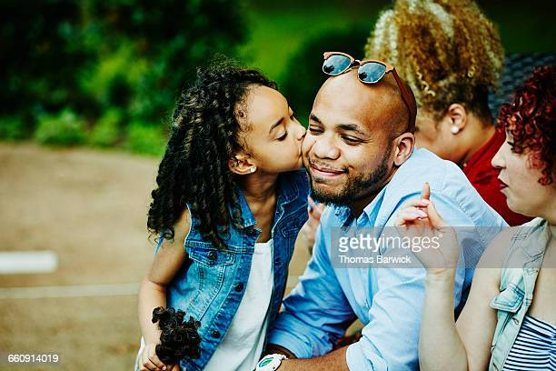Young girl kissing uncle on cheek during party