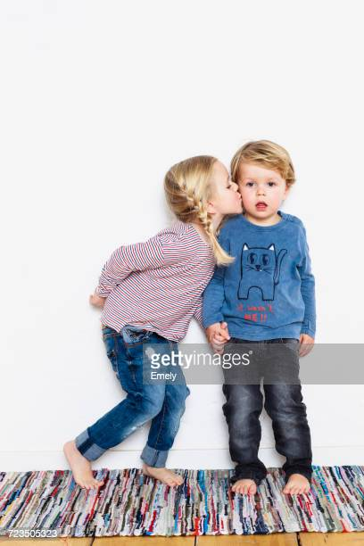young girl kissing young boy on cheek - nur kinder stock-fotos und bilder