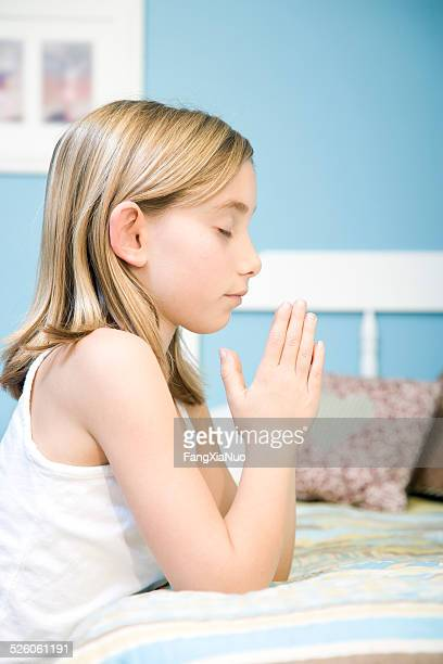 young girl kneeling near bed and praying - bible photos stock pictures, royalty-free photos & images