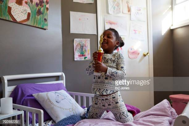 Young girl kneeling on bed kissing trophy