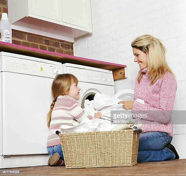 Young Girl Kneels on the Floor Helping Her Mum to Load Laundry Into a Washing Machine