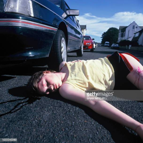 young girl knocked down by a car and lying on the road - of dead people in car accidents stock pictures, royalty-free photos & images