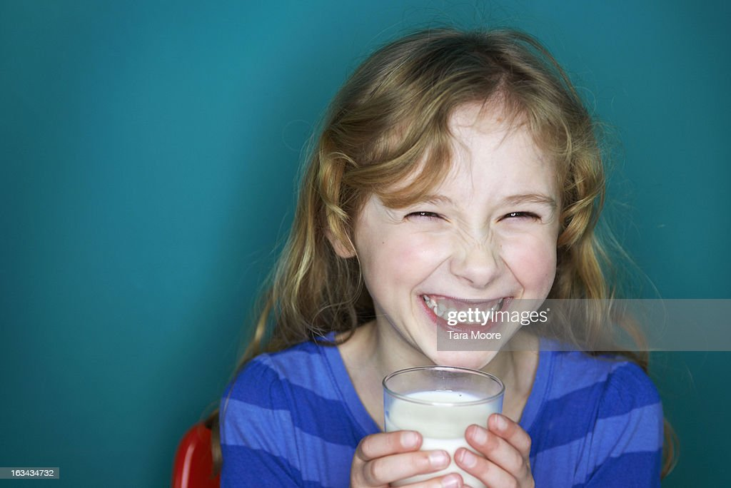 young girl laughing and holding glass of milk : Foto de stock