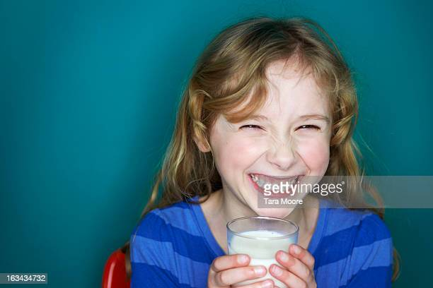 young girl laughing and holding glass of milk