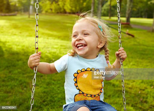 Young girl laughing on swing