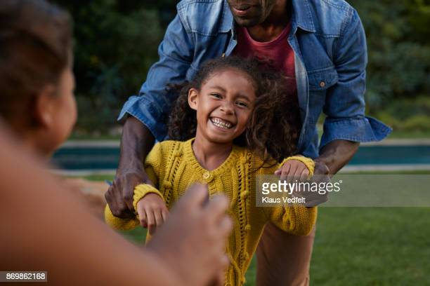 Young girl laughing while playing with her parents
