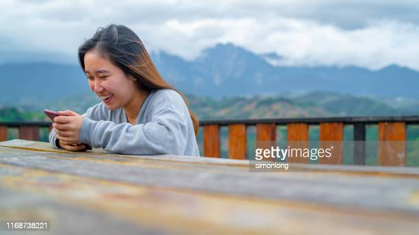 young girl laughing while using smartphone - サバ州 ストックフォトと画像