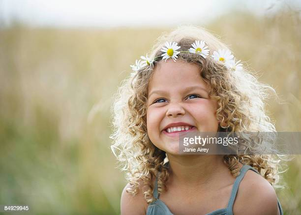 Young girl laughing with daisies in hair