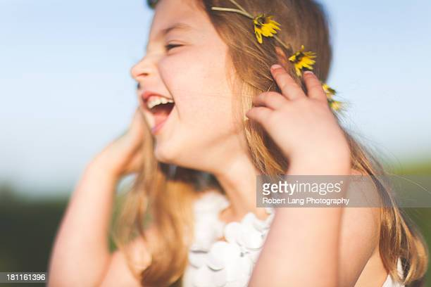 Young girl laughing with daisy chain in her hair