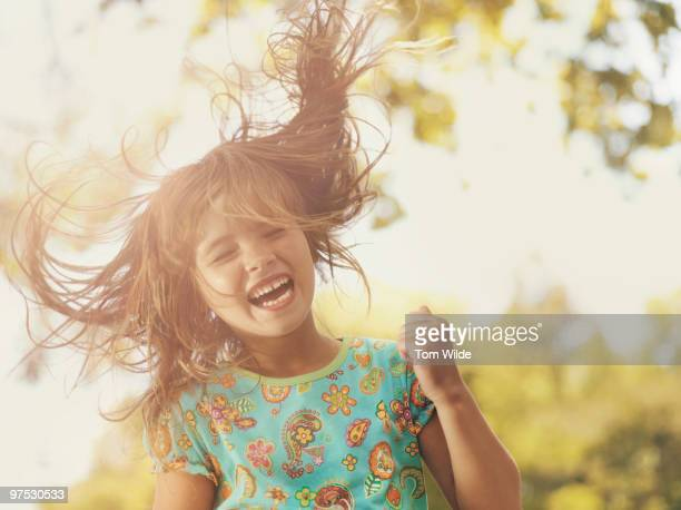 Young girl laughing with hair blowing