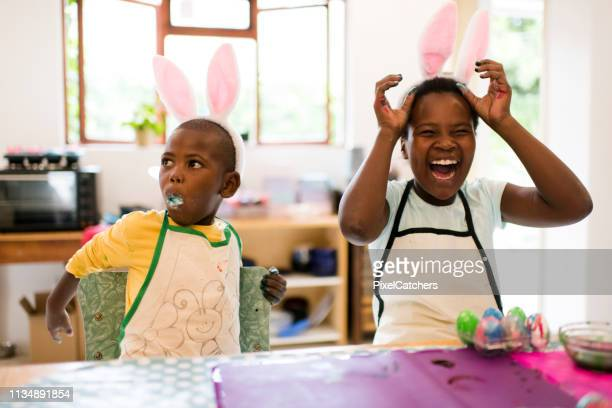 young girl laughs as boy puts whole easter egg in his mouth - easter photos stock pictures, royalty-free photos & images